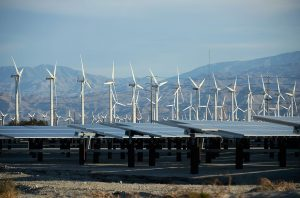 PALM SPRINGS, CA - MARCH 27:  Giant wind turbines are powered by strong winds in front of solar panels on March 27, 2013 in Palm Springs, California. According to reports, California continues to lead the nation in green technology and has the lowest greenhouse gas emissions per capita, even with a growing economy and population.  (Photo by Kevork Djansezian/Getty Images)