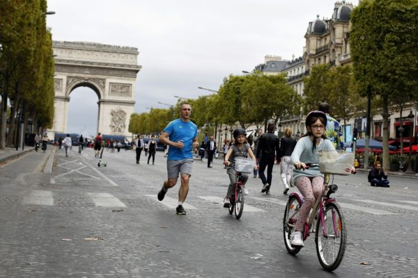 "A man runs as his daughters ride bicycle on the champs Elysees avenue, during the ""day without cars"", with the Arc de Triomphe in background, in Paris, Sunday, Sept. 22, 2019. It is the fourth year the city has held a car free day in an attempt to ease air pollution. (AP Photo/Thibault Camus)"
