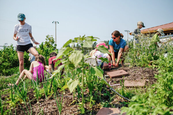 Fiona Jensen-Hitch, a FoodCorps service member, works in a garden with kids at a summer camp in Whitefish on July 14, 2021. Photo by Channing Johnson